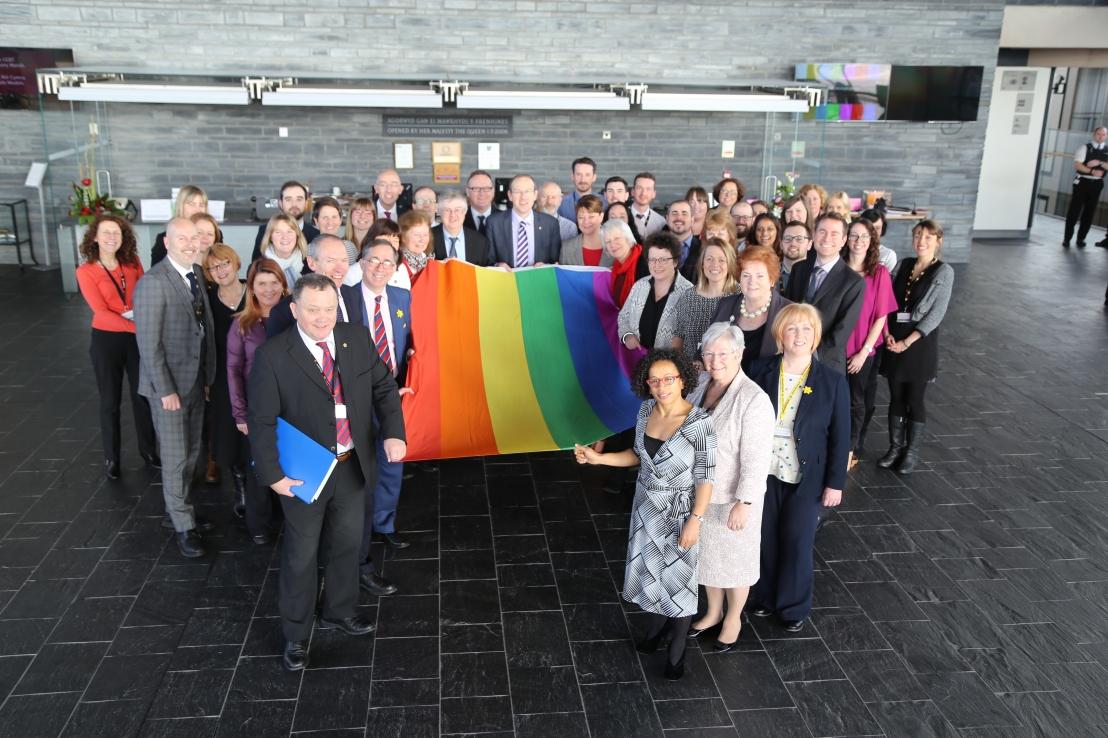 Llun staff LGBT y Cynulliad a Chyfeillion yn dal y faner enfys ar gyfer mis Hanes LGBT