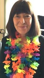 Ffotograff o Claire Clancy yn gwisgo coron o flodau'r enfys i baratoi ar gyfer Pride Cymru